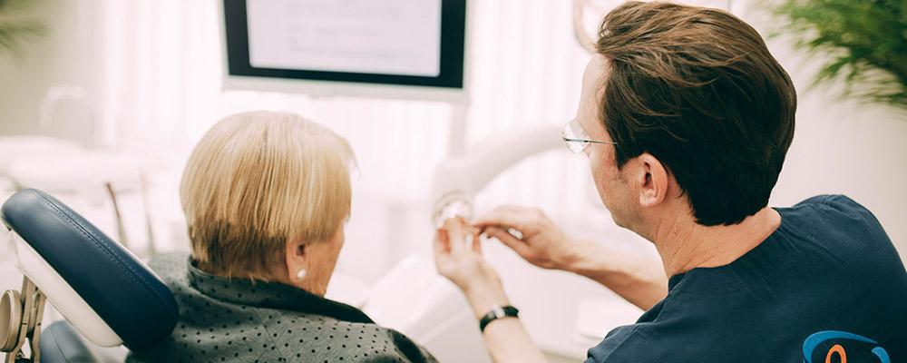 Dr. Sven Kurth erklärt Patientin, wie Zahnimplantate aus Berlin-Spandau ihr helfen.
