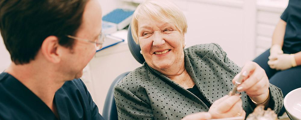 Patientin freut sich, dass sie bald mit festen Zähnen aus Berlin-Spandau wieder feste zubeißen kann