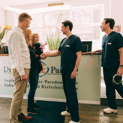 Zahnärzte begrüßen Familie in Zahnarztpraxis Berlin-Spandau.