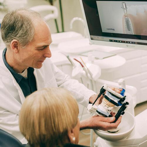 Zahntechniker zeigt Gebissmodell für perfekten Zahnersatz.