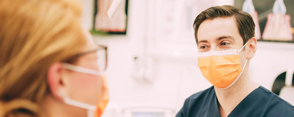 Zahnarzt mit Mundschutz lächelt nach einer erfolgreichen Füllungstherapie in Berlin-Spandau.