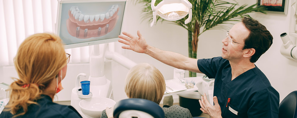 Dr. Sven Kurth zeigt Patientin die Vorteile einer Behandlung mit Zahnersatz auf Implantaten.