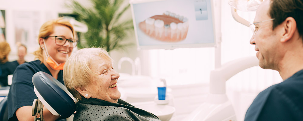 Ältere Dame freut sich über tolle Beratung für Menschen aus Falkensee bei Implantologen Dr. Sven Kurtgh